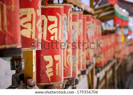 Red prayer wheels with Tibetan prayer inscription (focus on one wheel, rest blurred)