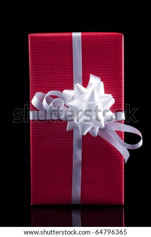 Red present isolated on black background - stock photo