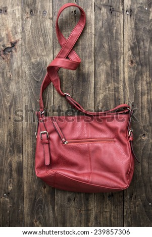 red purse on wooden background, from above - stock photo