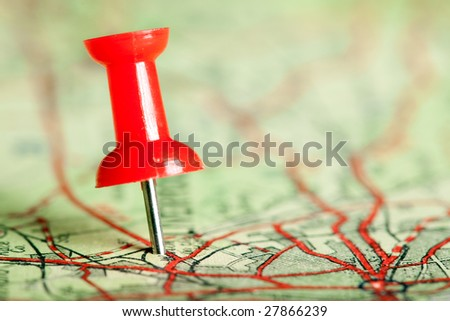 Red pushpin on a tourist map for travelling - stock photo