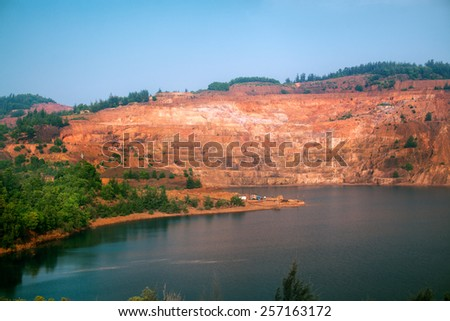 Red quarry lake in India - stock photo