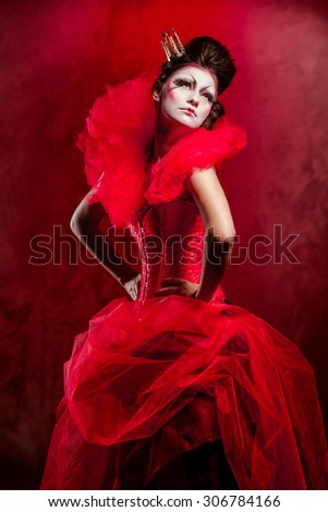 Red Queen. Woman with creative make-up in fluffy red dress posing indoors