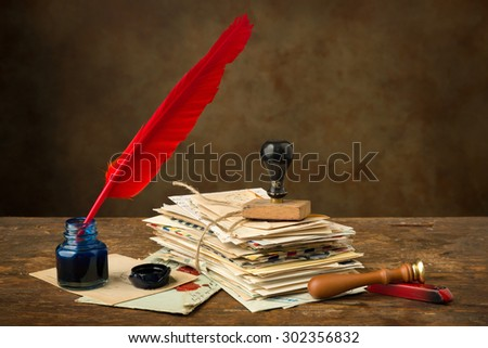 Red quill feather and ink well lying on an old table with nostalgic letters - stock photo