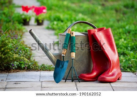 Red rain boots, watering can and garden tools closeup - stock photo