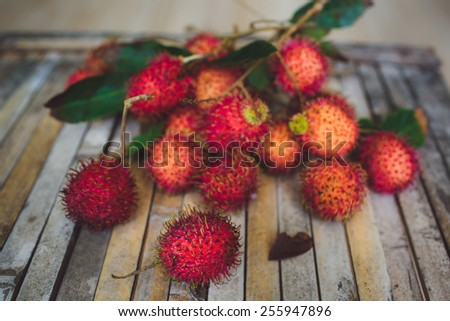 Red rambutan Nephelium lappaceum on broun board.  Fruit tropical tree of the family Sapindaceae , native to South - East Asia , cultivated in many countries in the region - stock photo