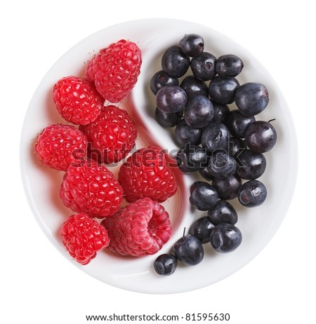 Red raspberry versus black bilberry in Yang Yin shaped plate, isolated on white - stock photo