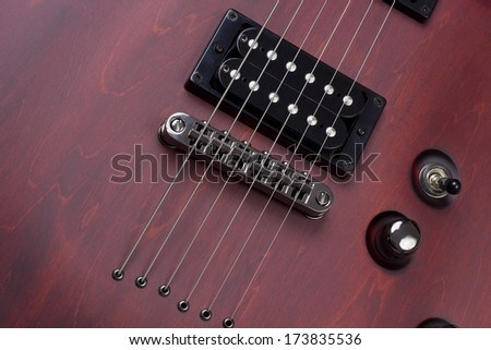 Red retro vintage wooden solid body electric mass production guitar with  strings and pickups background. Selective art focus - stock photo