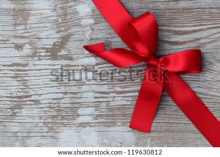 Red ribbon bow on wooden board with copy space