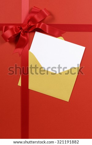 Red ribbon christmas gift background with gold envelope and blank greetings card, vertical