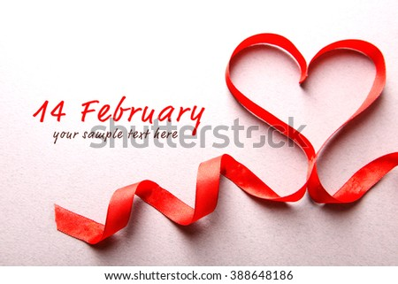 Red ribbon in shape of heart on light textured background - stock photo