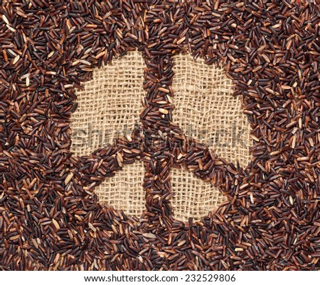 Red rice forming a peace symbol on burlap fabric  - stock photo