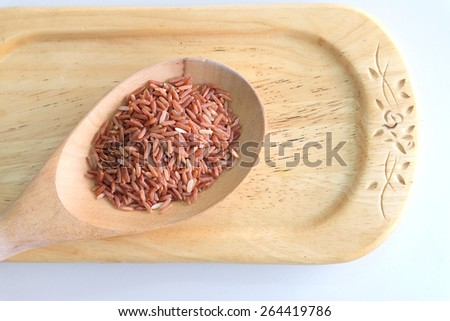 Red rice in a wooden spoon  - stock photo
