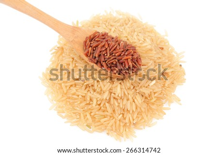 Red rice in a wooden spoon and pile of brown rice isolated on white background - stock photo