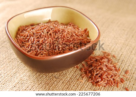 red rice in bowl on hessian fabric - stock photo