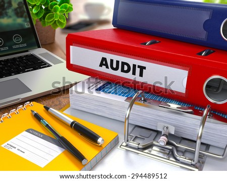 Red Ring Binder with Inscription Audit on Background of Working Table with Office Supplies, Laptop, Reports. Toned Illustration. Business Concept on Blurred Background. - stock photo