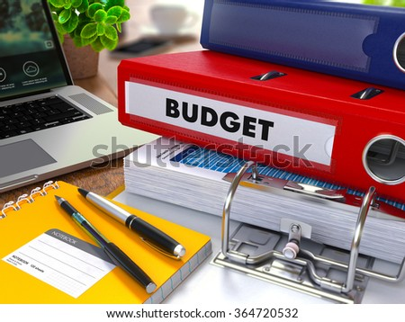 Red Ring Binder with Inscription Budget on Background of Working Table with Office Supplies, Laptop, Reports. Toned 3d Illustration. Business Concept on Blurred Background. - stock photo