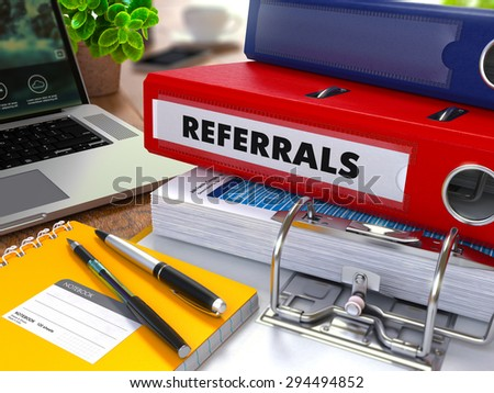 Red Ring Binder with Inscription Referrals on Background of Working Table with Office Supplies, Laptop, Reports. Toned Illustration. Business Concept on Blurred Background. - stock photo