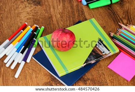 Red ripe apple close-up on school notebooks and some are multi-colored markers and pens on the wooden background