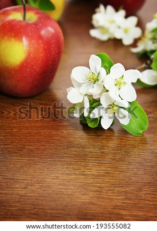Red ripe apple fruit and apple flower on the wooden table - stock photo