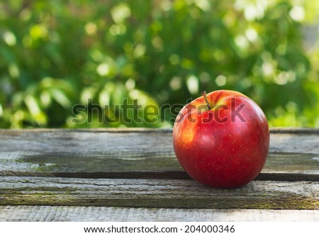 Red ripe apple outside on wood - stock photo