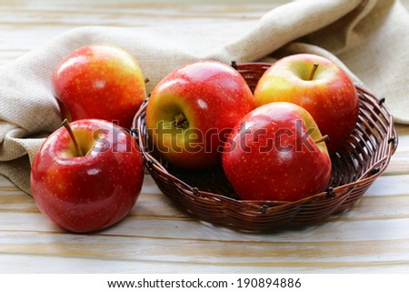 Red ripe apples in a wicker basket on a wooden table - stock photo
