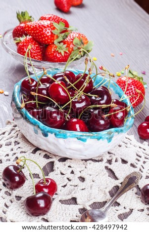 Red ripe strawberries in the glass bowl near the cherry bowl on knitted napkin on the gray table. Ripe cherries in handmade clay bowl and strawberries on the background - stock photo