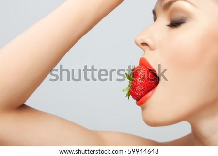 Red-ripe temptation. A portrait of a nude sexy woman holding a red-ripe strawberry in her mouth. - stock photo