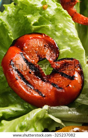 Red ripe tomato slice with grill stripes on a leaf of lettuce closeup