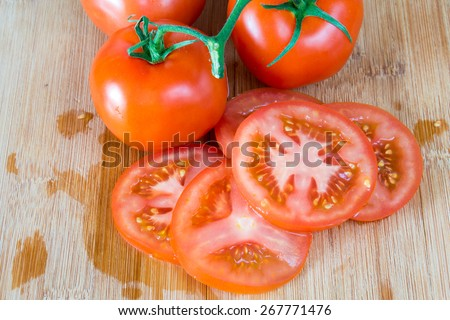 Red ripe tomatoes over a wooden cutting board,a more realistic approach to food ingredients, the beauty of the imperfect - stock photo