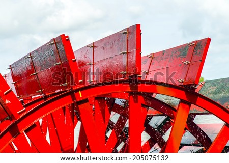 Red Riverboat Paddle Wheel in a River with Trees - stock photo
