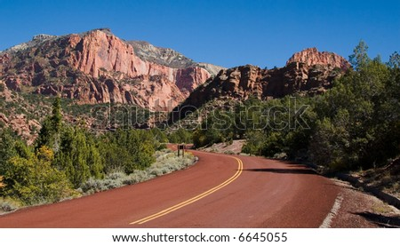 Red road leading to large monoliths formed by water erosion formed by the Virgin River n Zion National Park Utah