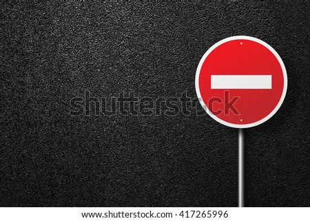 Red road sign of the circular shape. Behind the sign one can see a smooth asphalt road. No entry. The texture of the tarmac, top view. - stock photo