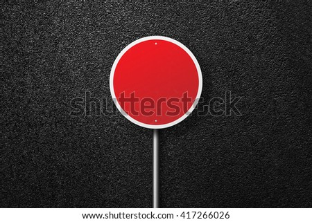 Red road sign of the circular shape. Behind the sign one can see a smooth asphalt road. The texture of the tarmac, top view. - stock photo