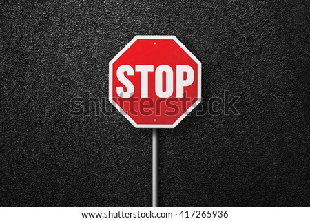 Red road sign with the words STOP. Behind the sign one can see a smooth asphalt road. The texture of the tarmac, top view. - stock photo