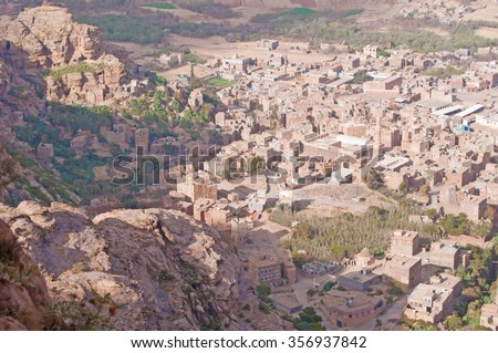 Red rocks and decorated old houses, overview of Shibam valley seen from Kawkaban, northwest of Sanaâ??a, fortified city, cities, village, street, Republic of Yemen, daily life - stock photo