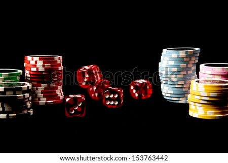 Red rolling dice and chips on a black background - stock photo