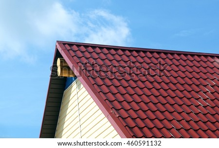 Red roof and wall covered with beige siding on country house in sunny day closeup