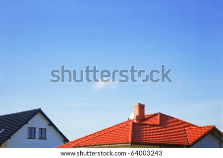 Red roof of new detached houses against blue sky. - stock photo