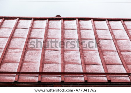 Red roof partially covered with snow