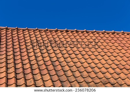 Red roof tile pattern over blue sky - stock photo