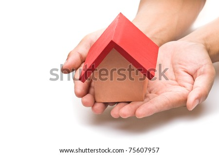 red roofed house over white in human hand - stock photo