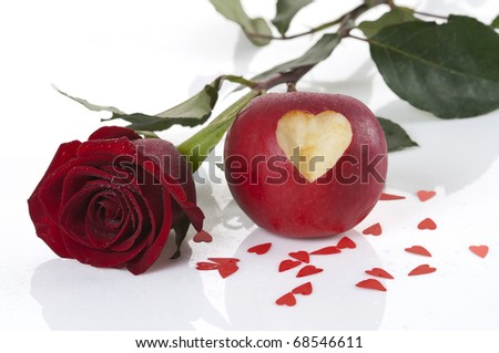 Red rose and apple with carved heart - stock photo