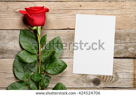 Red rose and greeting card on wooden background - stock photo