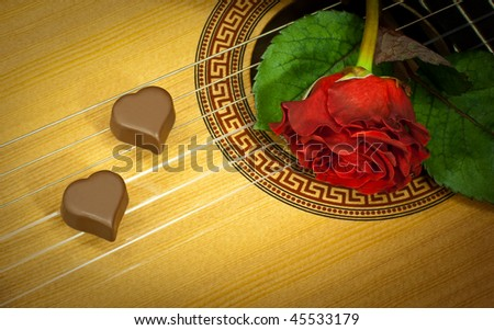 Red rose and two chocolate hearts on a guitar deck and strings, symbol of Valentine's day and romance - stock photo