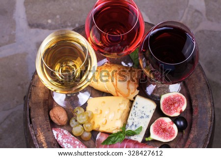 Red, rose and white  glasses and bottles of wine. Cheese, fig, grape, prosciutto and bread on old wooden barrel. View from above, top studio shot