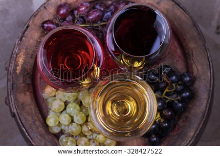 Red, rose and white glasses of wine with grape on old wooden barrel. View from above, top studio shot - stock photo
