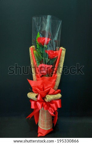 Red rose bouquet with bow tie on black background - stock photo