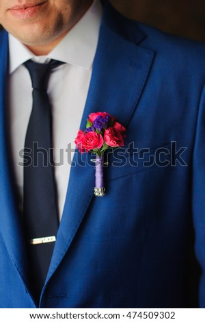 Red rose boutonniere on suit of the groom
