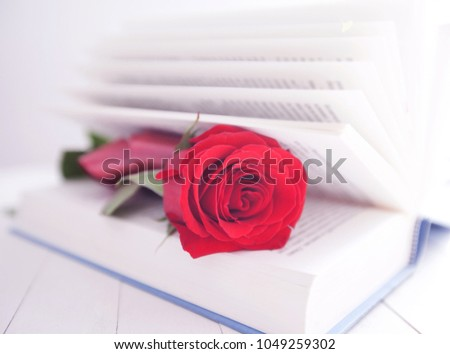 Red rose flower over open book on white wooden background, romantic and love, space for your message