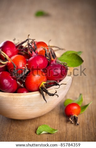 Red rose hips with green leaves in wooden bowl
